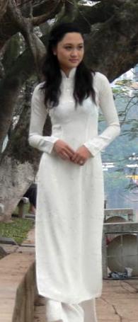 Une femme porte un áo dài blanc devant le lac Hồ Gươm à Hanoi.