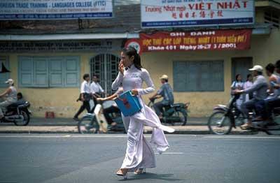 Étudiante traversant la rue, vêtue d'un áo dài.